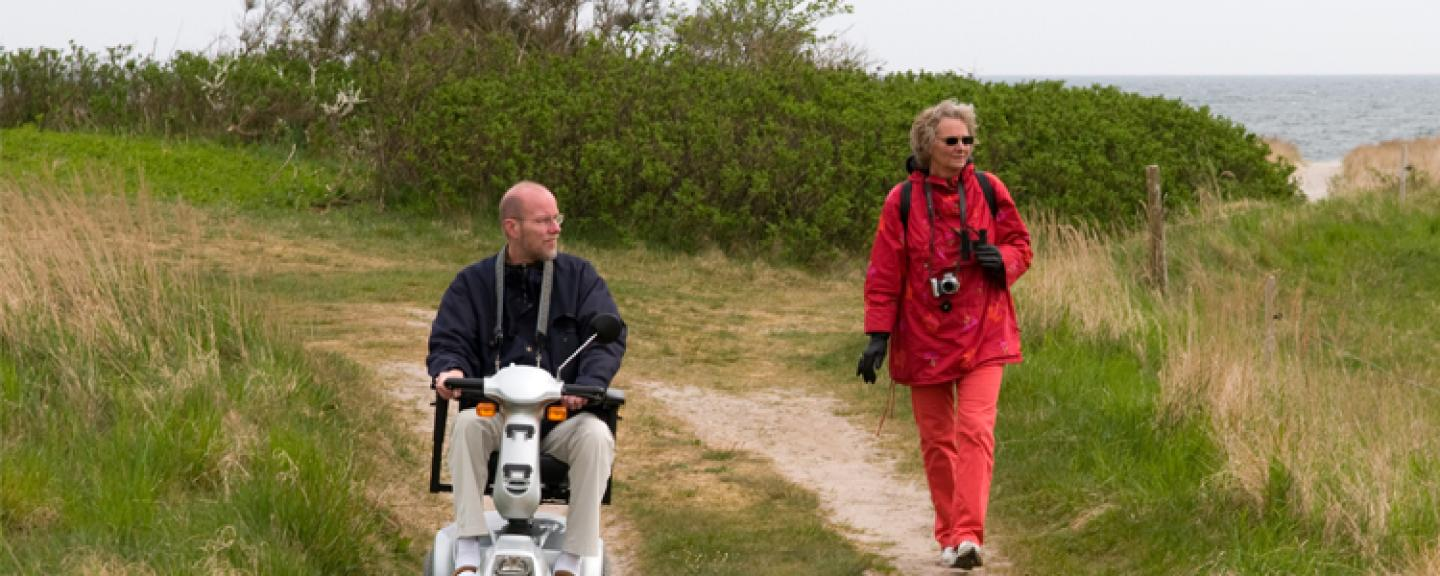 Couple experiencing accessible holiday using mobility scooter