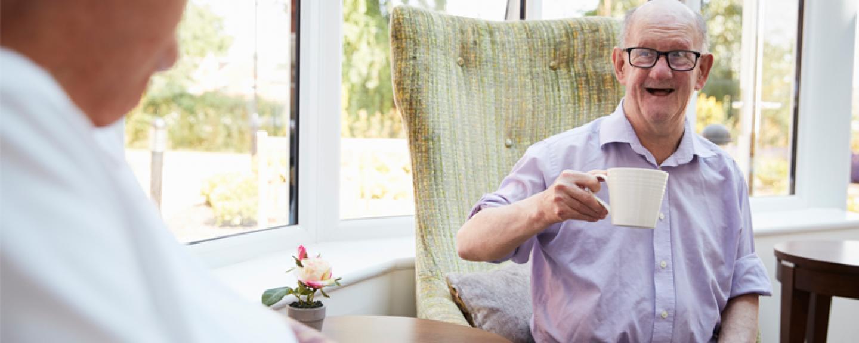 Man Talking to Elderly Disabled Man